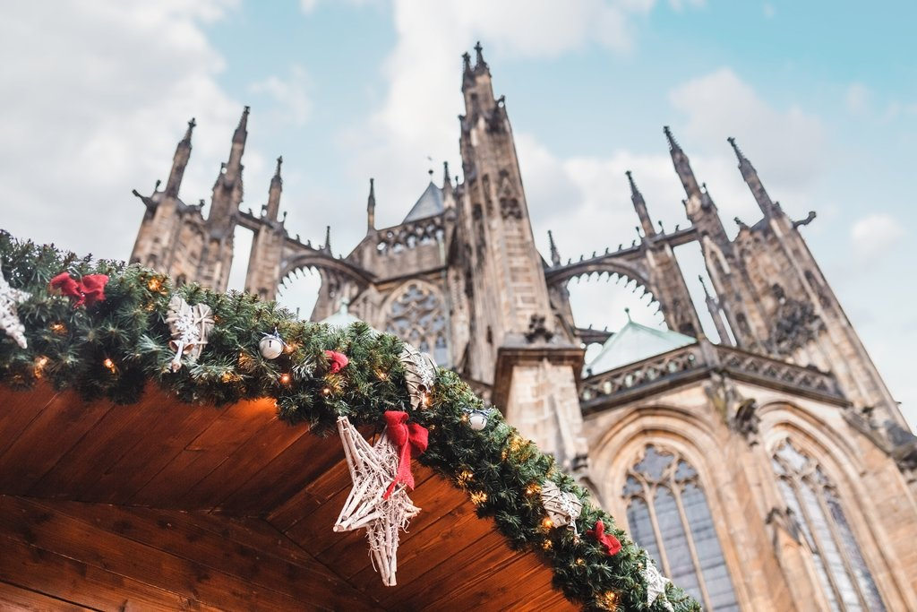 Rooftop of a Christmas stall decorated with a wreath and star in Prague Castle district behind St Vitus Cathedral