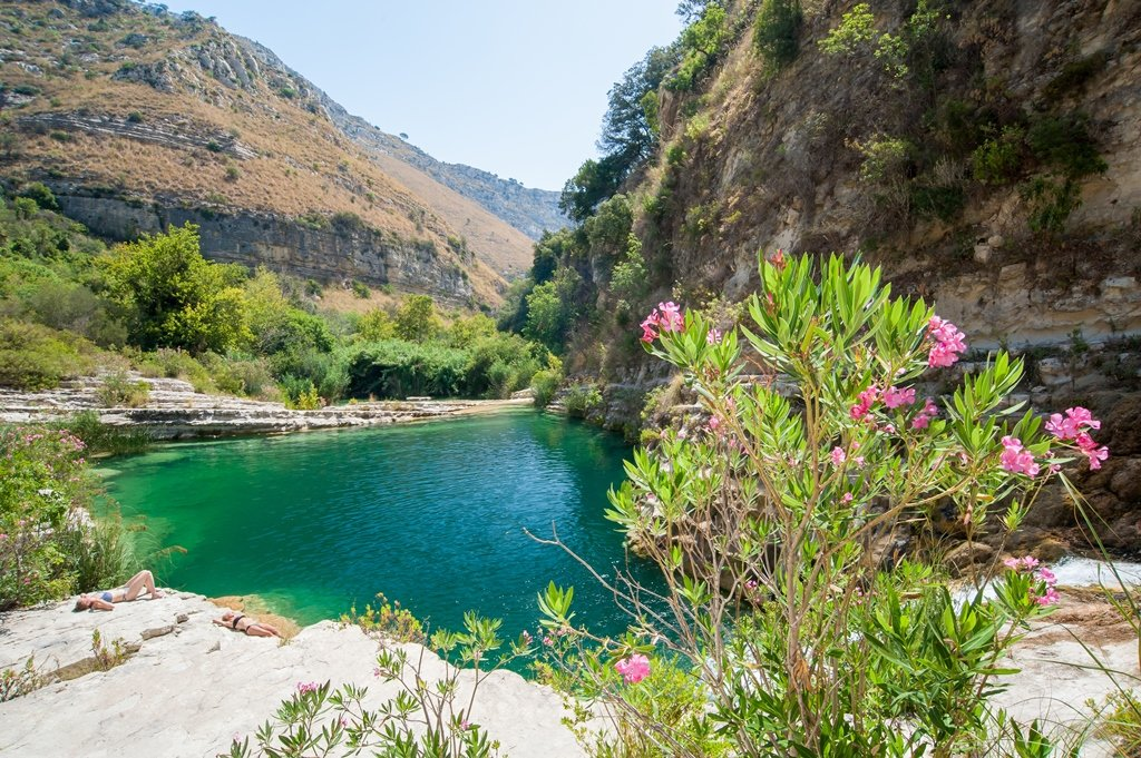 The emerald green lake at Cava Grande Natural Reserve in Sicily